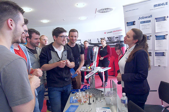 At the booth: Company representative of Mahle with a group of students