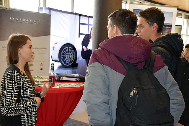 Daimler company representative in conversation with two students