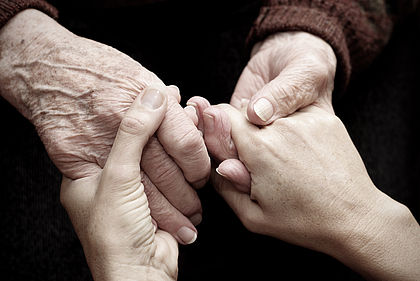 Close up of an old person and a young person holding hands