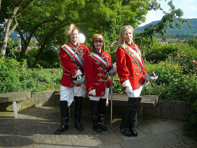 Drei Personen in roter Uniform