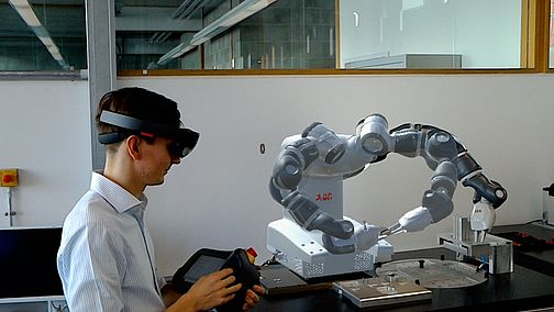 Student with VR glasses in front of a robot